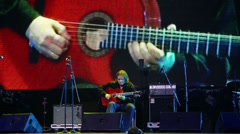 Roman Miroshnichenko plays guitar on stage with screen Stock Footage