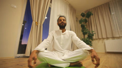 Indian man sitting on green mat and practicing yoga Stock Footage