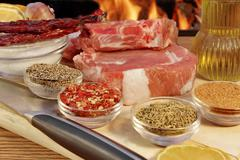 organic red raw steak sirloin and spice in fire background  - stock photo