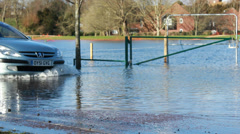 Uk severe floods, car passes playing field Stock Footage