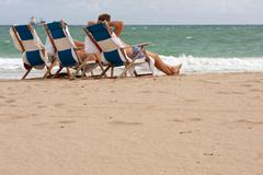 people relax in beach chairs on florida beach - stock photo