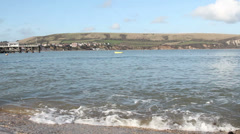 Small waves on the shore town and hills in back Stock Footage