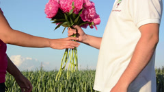 Couple of lovers meet  bouquet of peonies put on the back Stock Footage