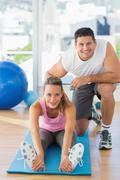 Stock Photo of Male trainer assisting young woman with pilate exercises