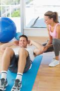 Female trainer looking at young man do abdominal crunches - stock photo