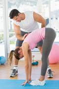 Male trainer assisting young woman with pilate exercises - stock photo