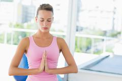 Woman with joined hands and eyes closed at fitness studio - stock photo