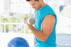 Sporty young man with dumbbell in gym - stock photo