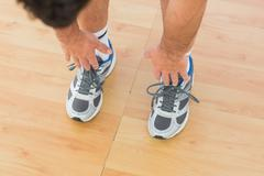 Sporty man stretching hands to legs in fitness studio Stock Photos