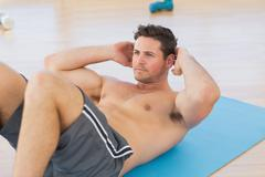 Determined young man doing abdominal crunches - stock photo