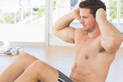 Determined man doing abdominal crunches at gym - stock photo