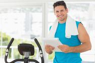 Stock Photo of Smiling trainer with clipboard in gym
