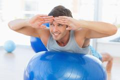 Stock Photo of Happy fit man stretching on exercise ball