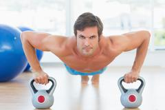 Serious young man doing push ups in gym - stock photo