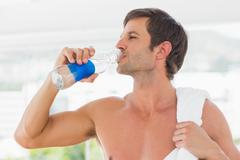 Shirtless man with towel drinking water Stock Photos