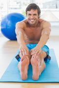 Stock Photo of Sporty man stretching hands to legs in fitness studio