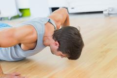 Stock Photo of Determined man doing push ups in gym