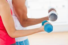 Stock Photo of Mid section of a sporty young couple with dumbbells