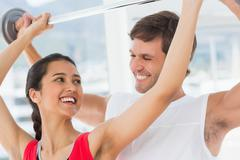 Male trainer helping fit woman to lift the barbell - stock photo
