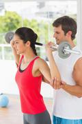 Male trainer helping fit woman to lift the barbell Stock Photos