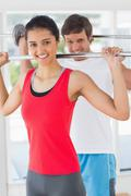 Stock Photo of Fit young man and woman lifting barbells