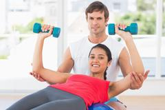 Stock Photo of Smiling instructor with woman lifting dumbbell weights