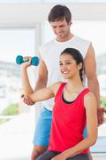 Instructor assisting woman with dumbbell weight - stock photo