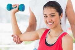 Instructor assisting smiling woman with dumbbell weight - stock photo
