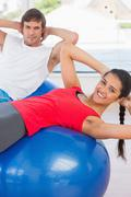 Fit couple exercising on fitness balls in gym - stock photo