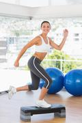 Stock Photo of Fit young woman performing step aerobics exercise