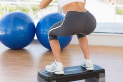 Stock Photo of Low section rear view of a fit woman exercising on step