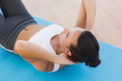 Stock Photo of Determined woman doing abdominal crunches on exercise mat