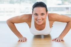 Stock Photo of Smiling beautiful woman doing push ups in gym