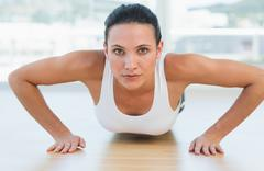 Stock Photo of Determined beautiful woman doing push ups in gym
