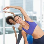 Stock Photo of Sporty people stretching hands at yoga class