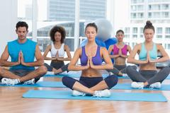 People in Namaste position with eyes closed at fitness studio Stock Photos