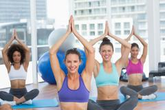 Sporty people in Namaste position at fitness studio Stock Photos