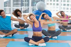 People with trainer doing pilate exercises - stock photo