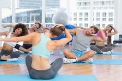 Stock Photo of People with trainer doing pilate exercises in a bright gymYoung people with