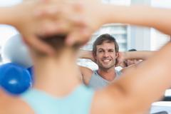 Stock Photo of Smiling male with blurred people doing stretching exercises