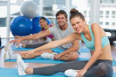 Smiling people doing stretching exercises - stock photo