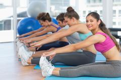 Sporty people stretching hands to legs in fitness studio - stock photo