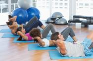 Stock Photo of Determined people doing sit ups in fitness studio