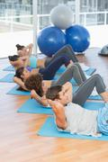 Determined people doing sit ups in fitness studio - stock photo
