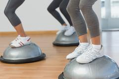 Stock Photo of Low section of fit people performing step aerobics exercise