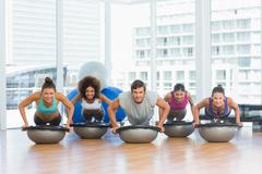 Stock Photo of Smiling people doing push ups in fitness studio