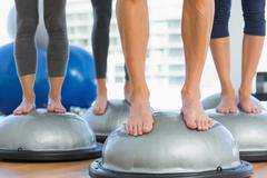 Low section of fit people standing on exercise equipment - stock photo