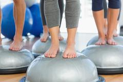 Stock Photo of Low section of fit people on exercise equipment