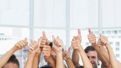Closeup of cropped people gesturing thumbs up - stock photo