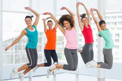 Fitness class and instructor jumping in fitness studio - stock photo